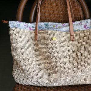 エコアンダリヤで手編みしたかごバッグ。内側にはLIBERTYプリントの巾着を取りつけてあります。